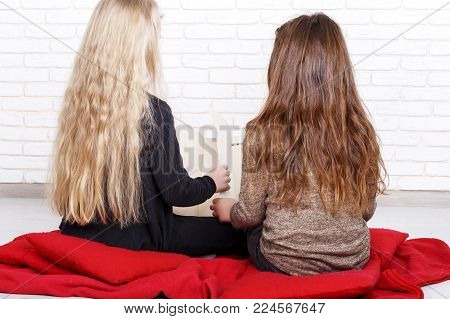 Two girls with the hope of adoption sit on a red blanket and read a book. Children dream of a family. Two children in anticipation of a miracle