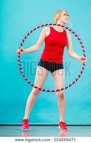 Fitness, sport, training and healthy lifestyle. Young woman in full length doing exercise with hula hoop, girl having fun playing game hula-hoop