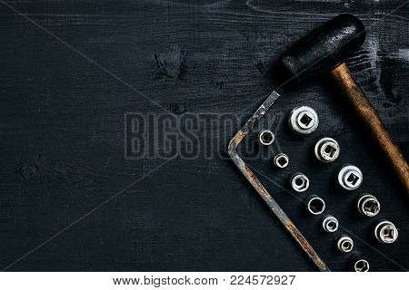 Copy space of working tools on a black wooden surface. Nippers, wrench keys, pliers, screwdriver, hammer. Top view. Still life. Flat lay