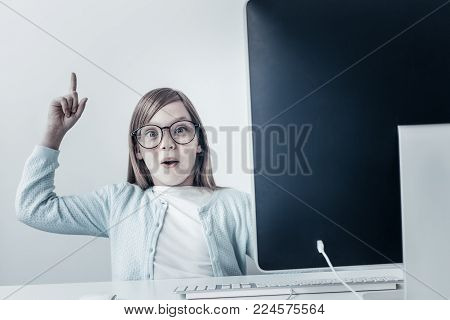 Ive got new plan. Cute schoolgirl looking at the camera with excitement while sitting at computer and generating new ideas at home.