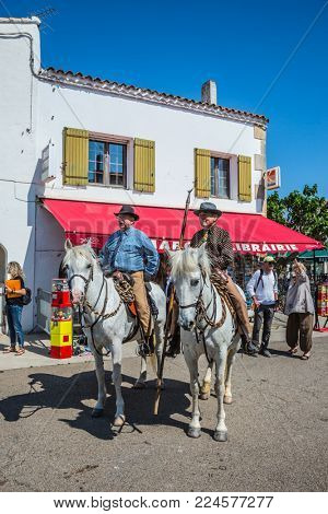 Sent-Mari-de-la-Mer, Provence, France - May 25, 2015. The concept of ethnographic and active tourism. Two guards on  white horses are waiting for the parade of World Gypsy Festival
