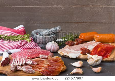 Chorizo, jamon and other Spanish meat appetizer on a black wooden background with spice.