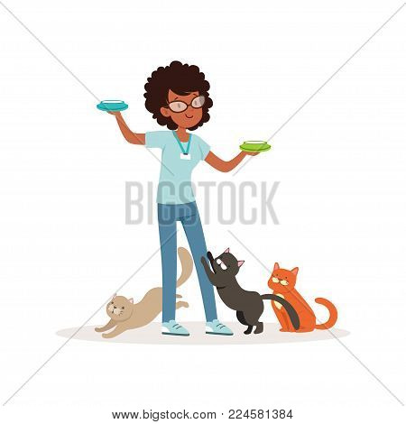 Cute curly-haired girl feeding group of homeless cats. Volunteer holding bowls with milk. Social help. Teen in glasses, blue t-shirt and jeans. Colorful flat vector design isolated on white background
