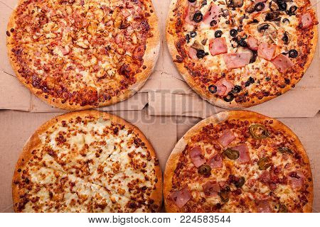 Top view of four fresh pizzas in cart boxes