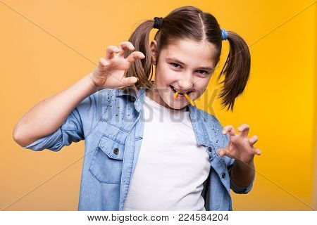 Cute teenage girl making fangs from food in studio photo on yellow background