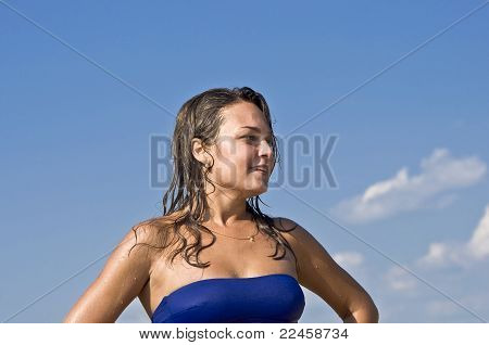woman in bikini smiling at the blue sky