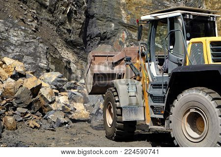 a wheel loader / front loader machine working on a heap of stones with its shovel at a quarry