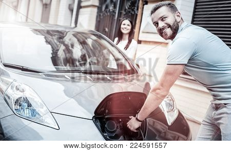 Easy and ecological transportation. Selective focus on a happy millennial guy grinning broadly while holding a charging nozzle and enjoying the process of his eco car supplying energy outdoors.