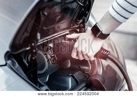 Contemporary lifestyle. Scaled up look on a young woman wearing smart wrist watch holding a charging nozzle while standing next to her electronic car and charging it outdoors.