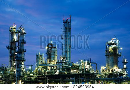 Glitter lighting of gas distillation tower plants on twilight sky, Close up of petrochemical industry