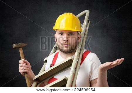 Clumsy worker standing with ladder and hammer