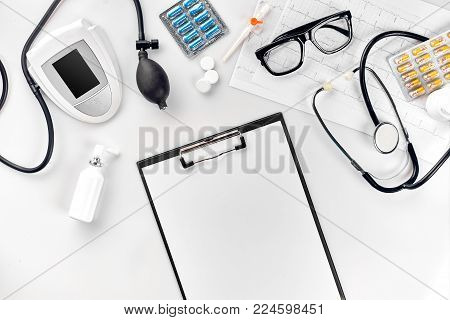 Top view of doctor's desk table, blank paper on clipboard with pen, stethoscope, electronic manometer to measure the blood pressure. Measure blood pressure set. Still life. Copy space. Flat lay