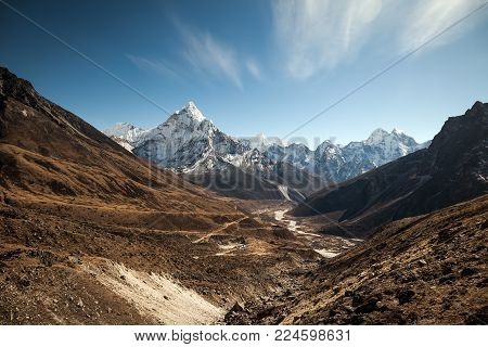 Ama Dablam mountain at sunset and blue sky. Sun illuminates slopes. Himalayan mountains, Nepal.