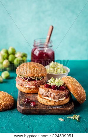Turkey Burger with Cranberry Sauce and Brussels Sprout Coleslaw, Turquiose Background, copy space for your text