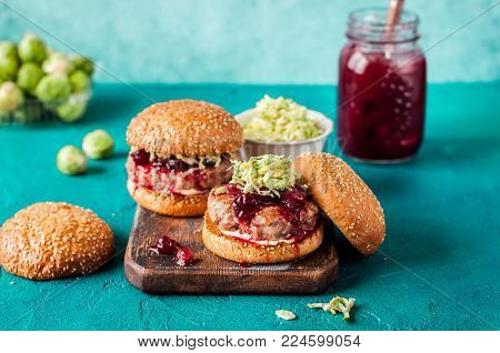Turkey Burger with Cranberry Sauce and Brussels Sprout Coleslaw, Turquiose Background