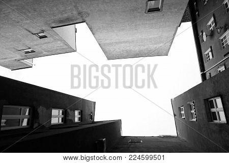 Look up at the multistory apartment house of angular shape. Empty place for text in the center. Black and white.