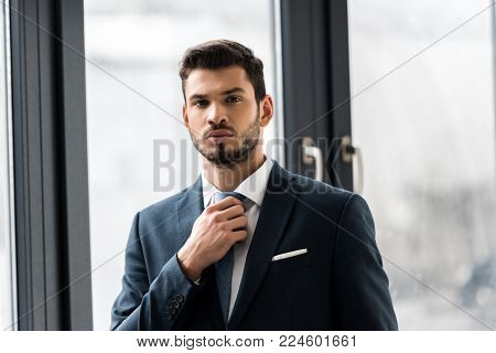 handsome young businessman adjusting necktie and looking at camera