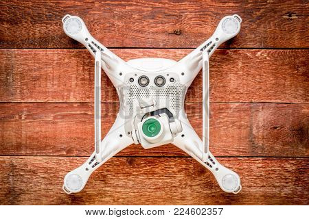FORT COLLINS, CO, USA - JANUARY1, 2017:  DJI Phantom 4 pro quadcopter drone on a rustic wooden table, bottom view showing a camera and sensors.