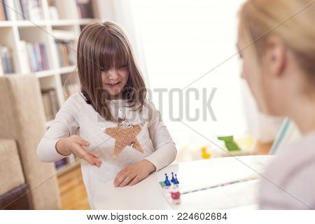 Mother and daughter sitting in a playroom, playing a ludo game; daughter rolling the dice