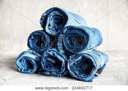 roll blue denim jeans on gray background