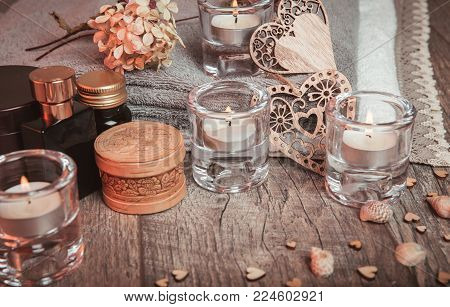 Spa concept in Valentine's Day, candles, handmade heart, dry flowers, seashells, setting for aroma therapy and massage on bed, relax and healthy care. Rustic style. Toned image in chocolate, tones.