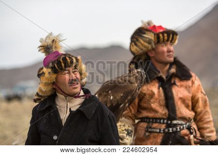 OLGIY, MONGOLIA - SEP 30, 2017: Eagle Hunter at traditional clothing, with a golden eagle on his arm during annual national competition with birds of prey
