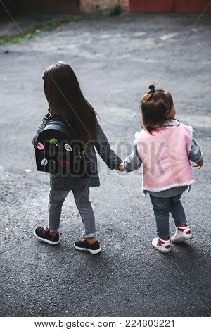 Little beautiful girls, stylishly dressed go for the hand on the asphalt. Relationships, people a