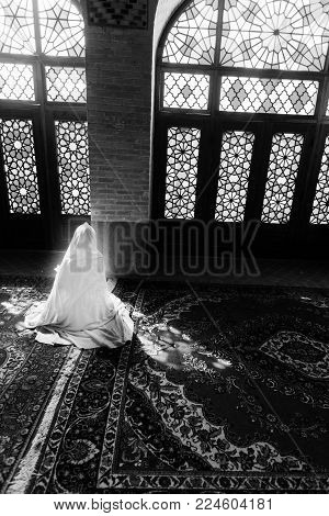 veiled woman in mosque in black and white