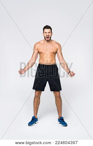 view of shouting young shirtless man on white