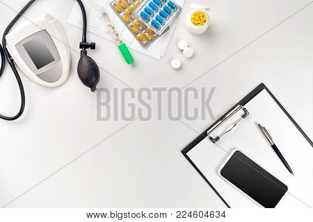 Top view of doctor's desk table, blank paper on clipboard with pen, electronic manometer to measure the blood pressure. Measure blood pressure set. Still life. Copy space. Flat lay