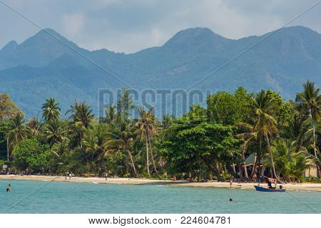 Koh Chang, Thailand - March 12, 2017: Tourists rest on the beautiful tropical beach on Koh Chang island in Thailand