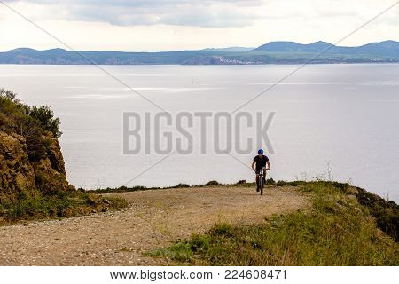 Theme Tourism And Cycling On Mountain Biking. Guy Rides Uphill On A Rocky, Rocky Road Against The Ba