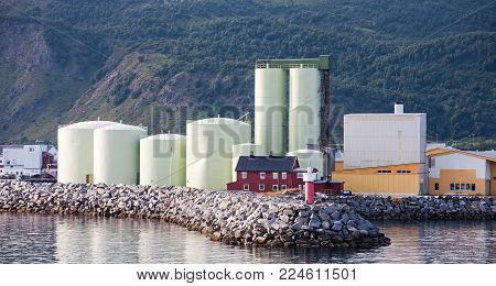 industrial building of fishing factory complex on mountain and sea nature background