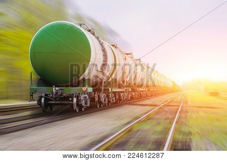 Freight train passing oil-loading, fuel oil, fuel tanks in motion