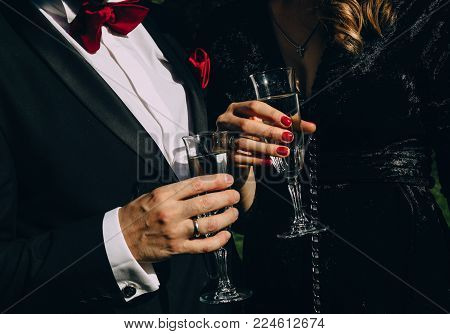 party style man in black suit red butterfly woman in black clothes red manicure drink champagne