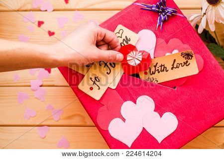 valentine's day holiday. red box for valentines with paper hearts. valentine messages and gift cards. female hand with paper heart