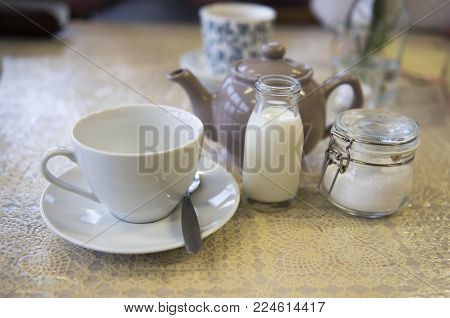 Cup and saucer with a teapot, milk and sugar, in a café setting