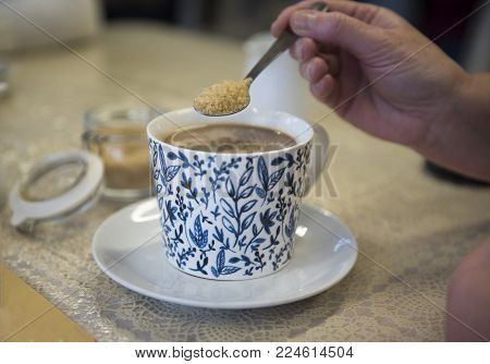 Unrecognisable hand putting a spoonful of brown sugar into a cup of coffee