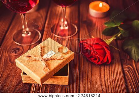 Composition of red rose, wine glasses, giftbox and wedding ring on wooden table. St. Valentine's Day concept.