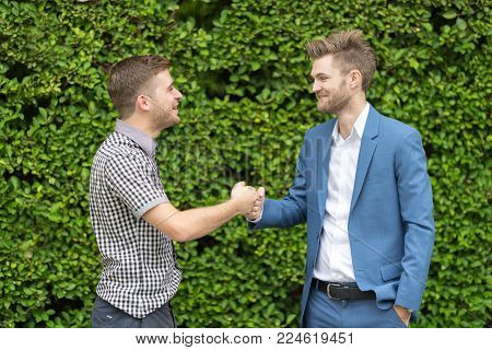 Handsome youg businessmen giving fist bump after business achievement - teamwork concept