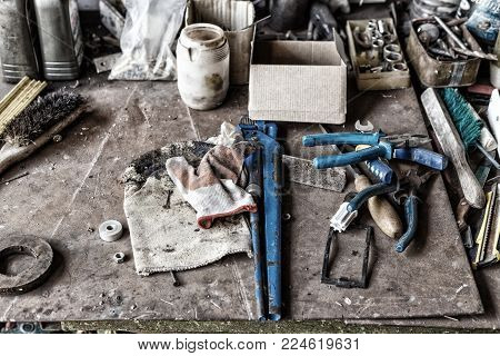 uncleared workshop with tools. on the dirty stone table scattered tools