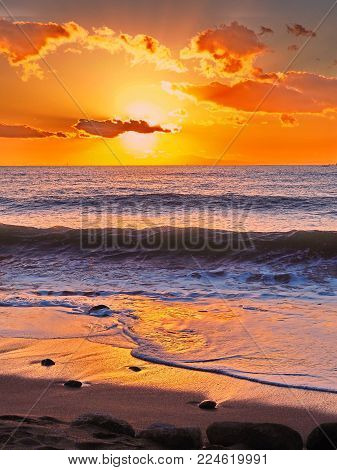Blazing burnt orange beach sunset with breaking wave and reflective wet sand, cloud parts the sun to create the warm tropical feeling. Details include swirling incoming surf, and pebbles in the sand. Just looking at this makes you want to pack your bags a