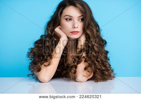 thoughtful young woman with long curly hair