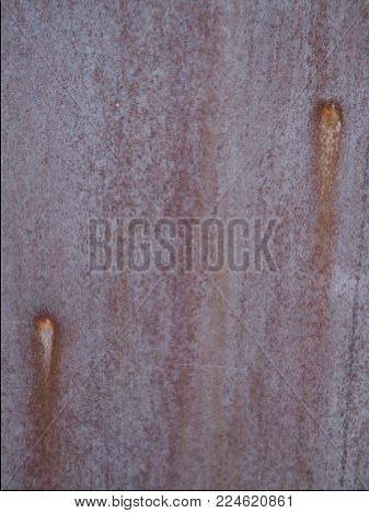 Rusty steel streaky  textured wall with two highlight spots for background. Natural streaky brown rusted steel metal wall, with two highlight hot spots. Great textured background with an industrial, antique, vintage, abstract, mechanical,