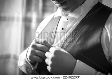 a bridegroom prepares for a wedding and dresses his vest and jacket in black and white. a future husband closes the button on his jacket for the wedding.