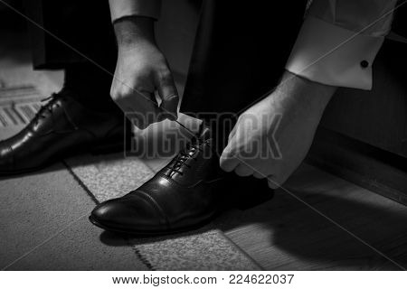 Bridegirl binds his shoes in black and white. a future husband tightens up for a wedding by putting on his shoes and tying his ties.