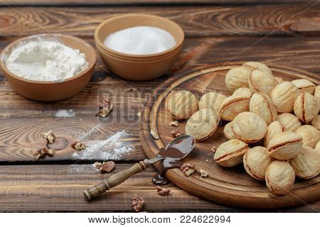 homemade cookies, nuts with condensed milk on wooden background. rural style. a spoon with condensed milk