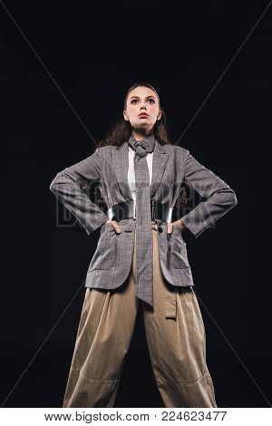 low angle view of confident young woman with hands on waist posing isolated on black