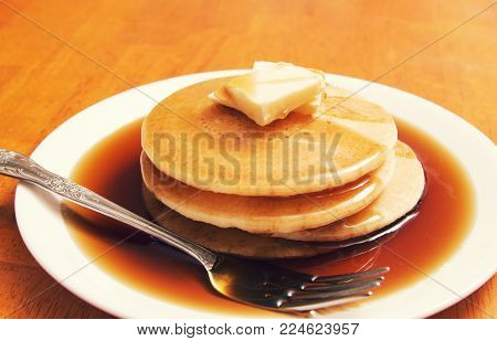 a breakfast meal plate of pancakes with syrup.