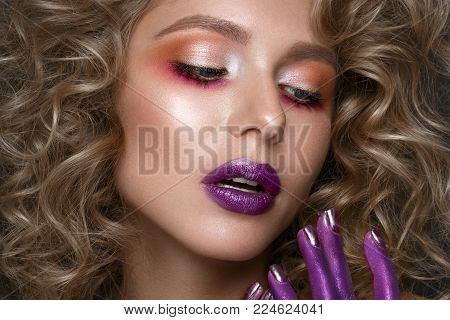 Beautiful blonde girl with curls and art creative make-up. Beauty face. Photos shot in the studio.